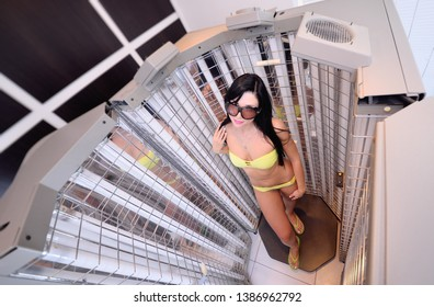 cute girl in a swimsuit in a special cabin with UV lamps for the treatment of psoriasis. Light therapy, phototherapy