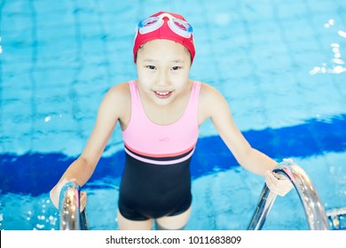 Cute girl in swimsuit and swim-cap going out of swimming-pool while holding by grab bars of ladder