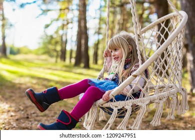 Cute girl swinging in a hanging chair in the woods in autumn