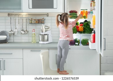 Cute girl taking apple out of refrigerator in kitchen