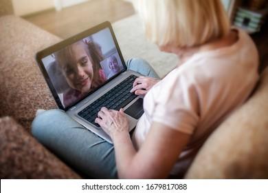 Cute Girl spricht mit ihrer Großmutter im Video-Chat auf Laptop, digitales Gespräch, Leben in Quarantäne, Selbstisolation