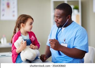 Cute girl with teddybear looking at clinician at hospital