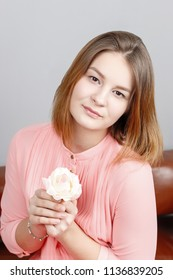 Cute girl teenager in pink dress sits with white rose in studio