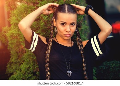 Cute girl teenager with two pigtails hair braids posing for camera