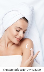 Cute girl with thick eyebrows and perfect skin at white background, towel on head, beauty photo concept, skin care, spa concept, using night cream.