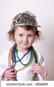 Cute Girl Toddler Wearing Mardi Gras Beads and a Jeweled Tiara