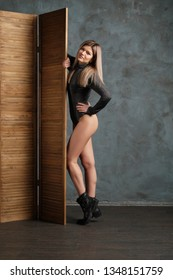 Cute girl in top, leather shorts and dense tights posing near folding screen