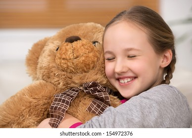 Cute girl with toy bear. Cheerful little girl hugging toy bear and smiling