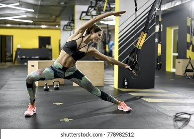 Cute girl is training with TRX straps in the gym. She does a stretching exercise. Woman wears colorful pants with black top and pink sneakers. Horizontal.