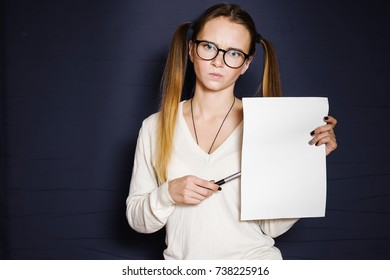 cute girl with two ponytails and with glasses points to A4 sheets of paper, isolated on a blue background