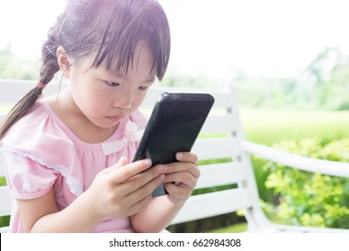 cute girl use phone in the park