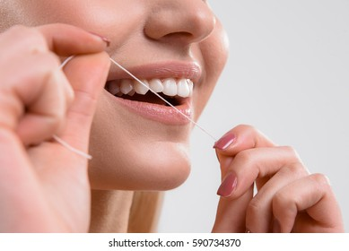 Cute girl using dental floss