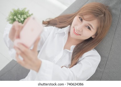 Cute girl waking up early to play mobile on the cushion,Selfie concept