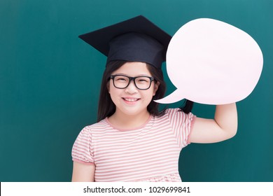 cute girl wear bachelor cap with speech bubble and blank green chalkboard