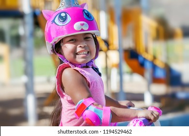 Cute girl wearing cat helmet and protective pads while learning to ride a bicycle is smiling in a kids playgound