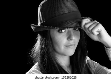 Cute Girl Wearing A Hat - This is a black and white image of a cute young woman wearing a fedora. Shot on a black background.
