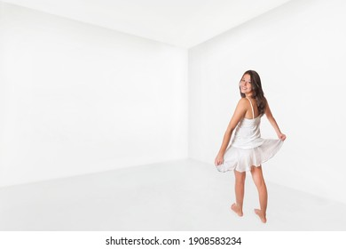 Cute girl wearing skirt and top and dances happily in an empty white room