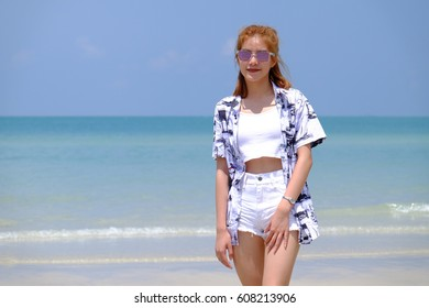 a cute girl wearing sunglasses on the beach in Thailand