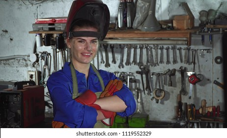 cute girl welder in uniform in the garage in the background of the workbench . Women's work