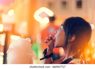 Cute girl with white cotton candy and night light