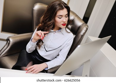 Cute girl in a white shirt is sitting at the computer monitor. Office worker, director, secretary, bitch, manager