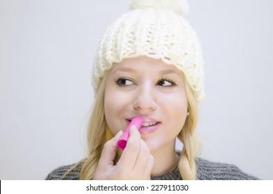 Cute girl white winter cap applying lip balm