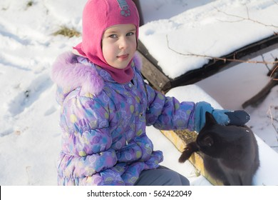 Cute girl in winter snow playground with sleds outdoors