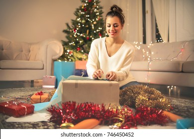 Cute girl wrapping Christmas gifts