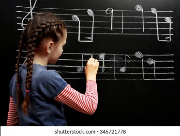 Cute girl writing at the blackboard with musical notes, in the classroom