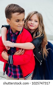 cute girlfriend hugs a guy from behind in the street in the city. Two children together embrace. School love, kids fashion models. Red jacket, blue skirt.