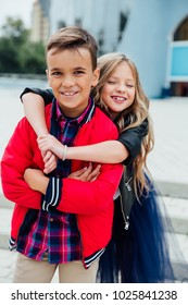 cute girlfriend hugs a guy from behind in the street in the city. Two children together embrace. School love, kids fashion models. Red jacket, blue skirt.Happy smile emotionally.
