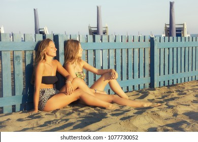 Cute girlfriends sitting on sand in summer