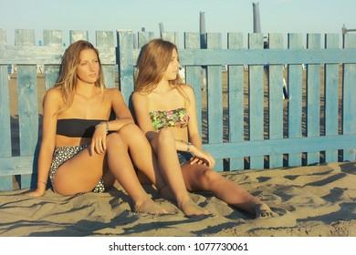Cute girlfriends sitting on sand in summer