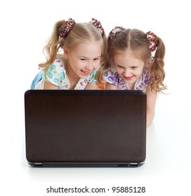 cute girlfriends smiling and looking at the laptop