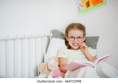 Cute girlie in glasses reading a book while lying in bed. Next to her sits a doll. Bright children's drawing on a white wall. The girl looks into the camera.