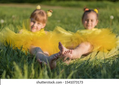 Cute girls of 6-7 years old in yellow tulle skirts lie on a green lawn with white dandelions in the summer in sunny weather. Feet close up.