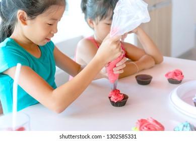 Cute Mädchen schmücken Cupcakes in der Küche während des Kochkurses. Asiatisches Mädchen, das Schokoladenkuchen mit rosafarbener Wischcreme schmückt. Kinder mit Süßigkeitsbeutel, die Buttercreme auf Cupcakes pressen.