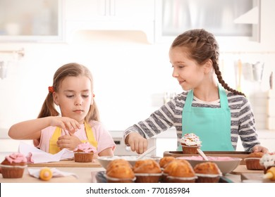 Cute girls decorating cupcakes in kitchen during cooking classes