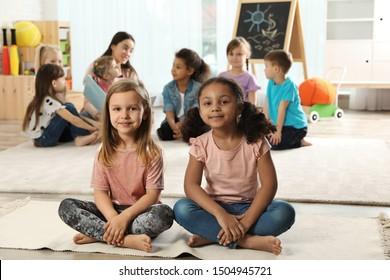 Cute girls sitting on floor while kindergarten teacher reading book to other children indoors