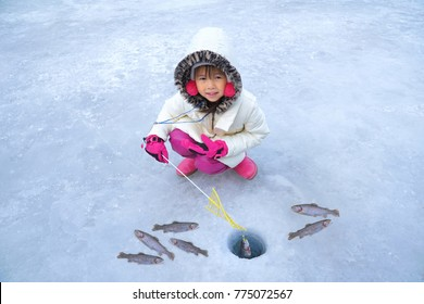 Cute girls are sitting on the floor of ice fishing. Ice Fishing Tournament. Ice Fishing Travel at the North Pole. Ice Fishing Tour at Antarctica.