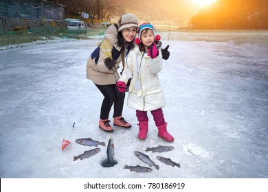 Cute girls are sitting on the floor of ice fishing.Ice Fishing Tournament. Ice Fishing Travel at the North Pole. Ice Fishing Tour at Antarctica.