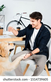 cute golden retriever giving paw to handsome and smiling man