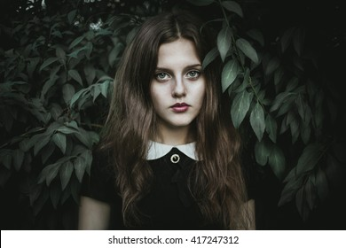 A cute goth girl wearing black dress stands amongst autumnal trees.Beautiful witch in the woods.Sad lonely girl.Beautiful eyes.