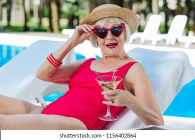 Cute grandmother. Funny cute grandmother with bright red lips drinking refreshing summer cocktail