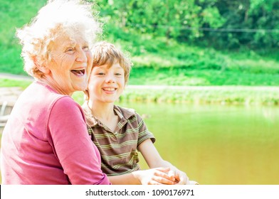 Cute grandmother and grandson laugh at the nature cheerfully. Family leisure