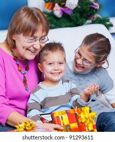 Cute Grandmother and her two grandchildren watching Christmas gifts