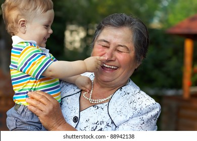 cute grandson grabbing the nose of laughing great grandmother. funny outdoors