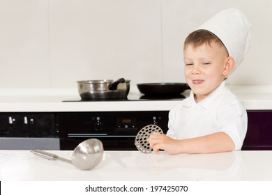 Cute grinning little boy in a chefs hat and apron standing behind a kitchen counter with his utensils ready to start cooking