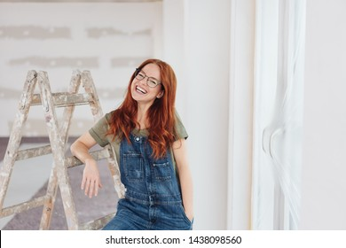 Cute grinning young DIY woman wearing glasses standing leaning on a ladder in an unpainted room in her new home