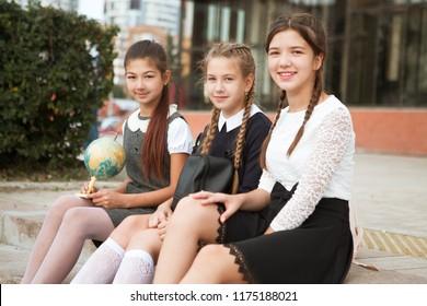 cute group girls teenages sitting outside school buildings